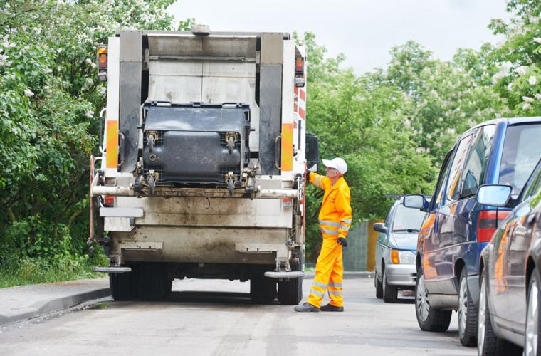 A man in orange jumpsuit operating a rubbish truck
