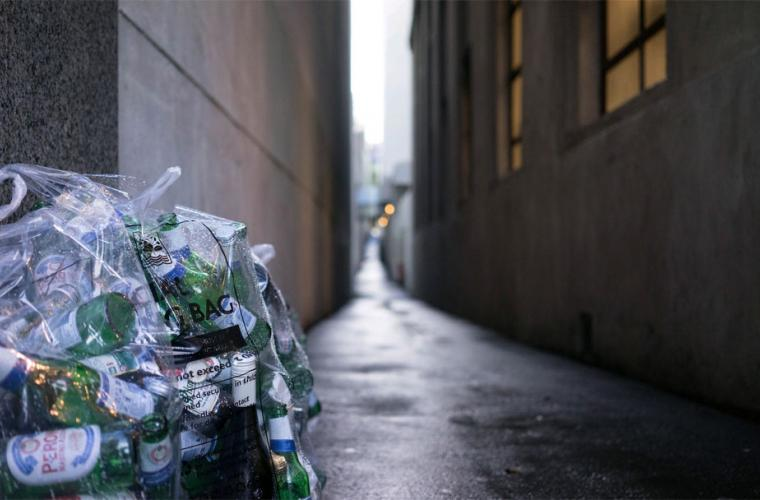 Photo of empty glass bottles in clear recycling bag